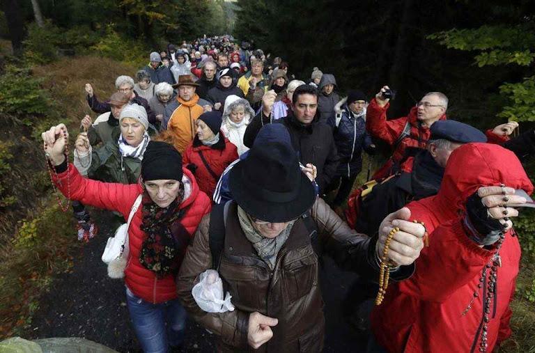 Poloneses rezam caminhando na floresta de Szklarska Poreba, fronteira com a Republica Checa