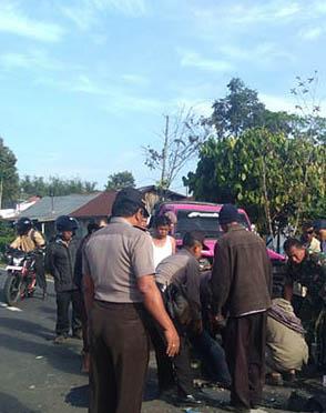 Polisi dan warga mengevakuasi korban kecelakaan yang menewaskan seorang pengiujil.