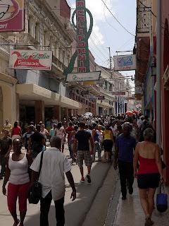 Santiago de Cuba, Fußgängerzone in der Altstadt. In der engen Straße drängen sich die Menschen, darüber viele Reklameschilder.