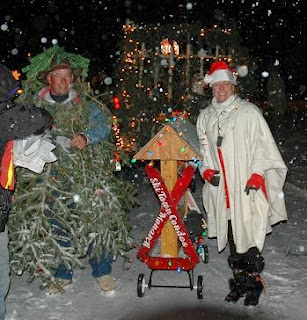 Winter snowy evening at a parade with a man dressed up as a Christmas tree and a lady dressed up as Mrs. Claus standing next to a mini Ski Town Condos float with Christmas lights shining.