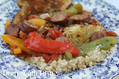 A sausage and peppers dish, using spicy Cajun sausage, pan seared cabbage wedges, sweet onion and diced tomatoes with green chilies, served over rice.