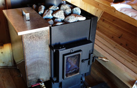 Sauna stove too right next to wooden benches.