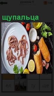 На тарелке приготовлены щупальца кальмара и вокруг лимон, батон белого хлеба и зелень