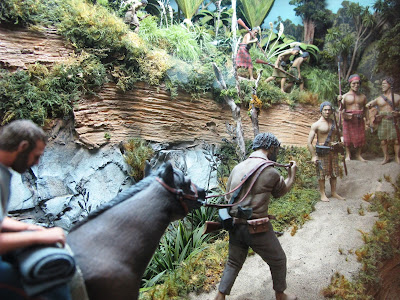 Diorama of a 19th-century man on the back of a horse in the bush,being lead up a track by a Maori.