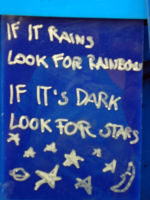 "Sculpture graffiti, ""If it rains look for rainbow. If it's dark look for stars.  White on navy blue, illustrated with stars, Saturn, and a crescent moon."