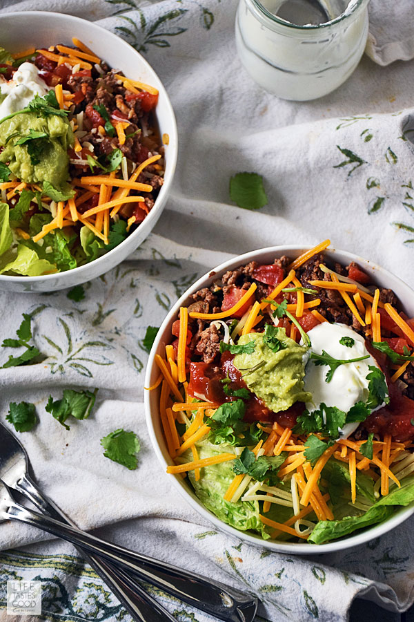 Taco fixings served over rice in a bowl topped with guacamole and sour cream