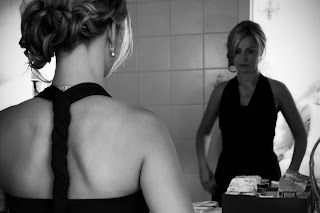 bridesmaid getting ready, looking at herself in the mirror