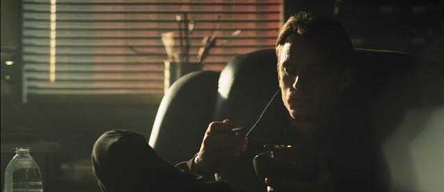 el protagonista comiendo un tazón de cereales, también vemos una botella de agua, la luz proviene de una ventana al fondo de la escena