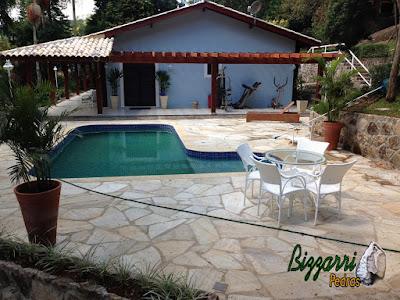 Construção de piscina de concreto revestida de azulejo em residência em condomínio em Atibaia-SP com o pergolado de madeira, o muro de pedra e o piso da piscina com pedra São Tomé tipo caco.