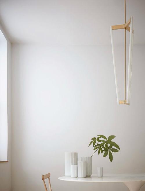 Lyngby Vasen stehen auf einem Tisch, über dem eine Lampe vom Designer Michael Anastassiades hängt