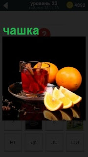 На блюдце стоит прозрачная чашка с напитком, внутри которого трубочки и рядом нарезаны дольками фрукты