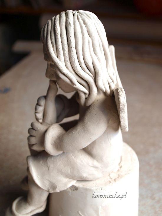 Ceramiczny aniołek ze skrzydełkami i fletem.