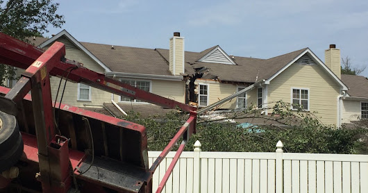 Extensive damage to a home after a boom truck owned and operated by Big Woody's Tree Service overturned onto the house in Chattanooga, Tennessee