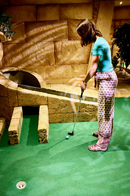 Abbey stands taking a shot during a game of mini golf in front of an ancient temple themed hole