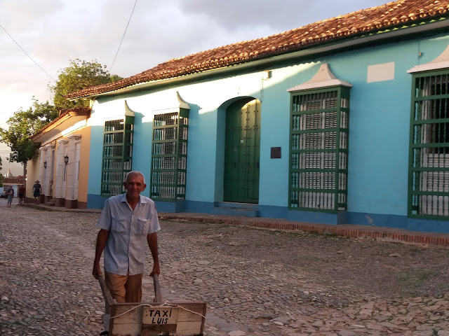 A man offering luggage transport services in Trinidad, Cuba