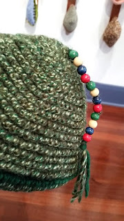 close up of a tweed coloured green hat which has a long tassel on the top. The tassel is decorated with 12 wooden beads in primary colours.