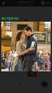 Мужчина и женщина встреча на вокзале на фоне табло с рассписанием