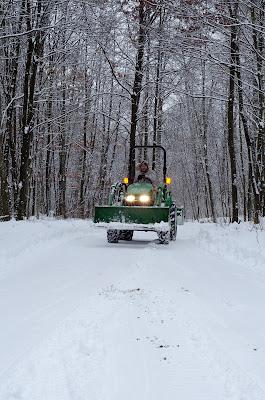 john deer plowing snow in winter