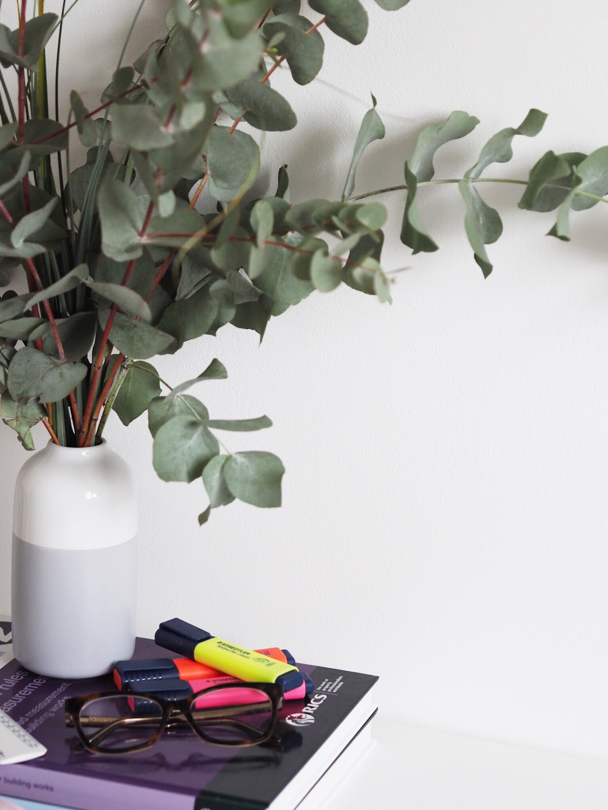 Portrait books, glasses, highlighters and vase of eucalyptus