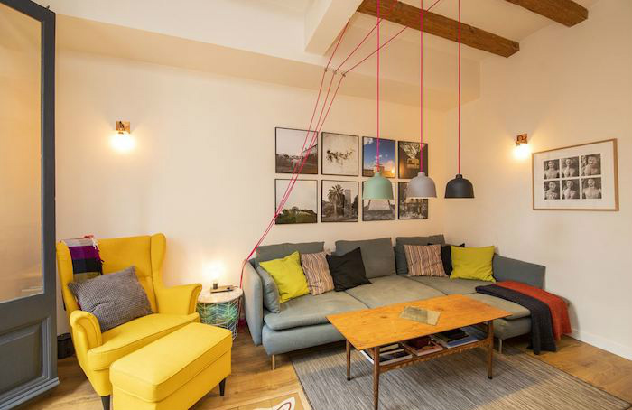 Cómo decorar un apartamento joven con poco dinero: salón con vigas y suelo de madera. Sofá y reposapiés amarillo