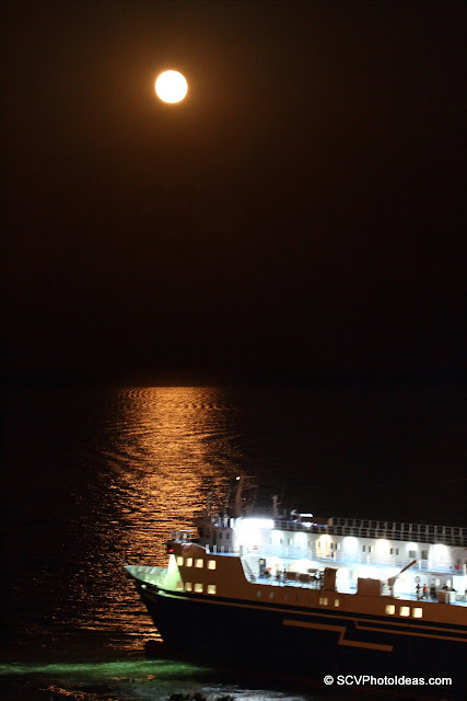 Ferryboat exiting harbor on moon reflections