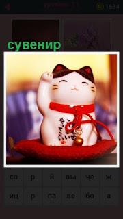 на подушке красного цвета сувенир в виде кошки с ленточкой