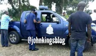 Policemen standing near their blue truck