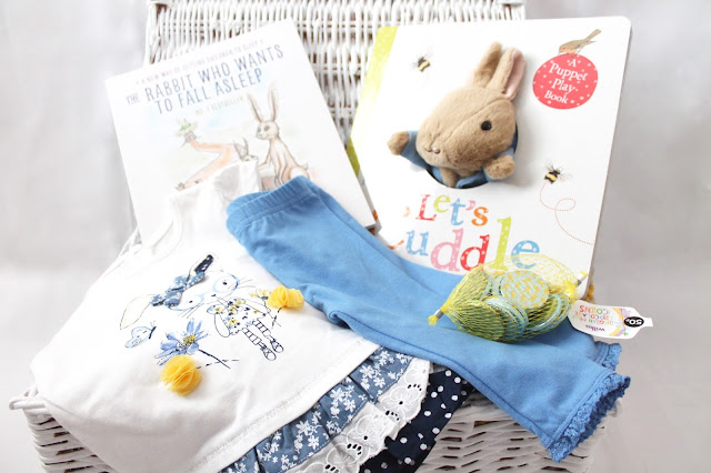 Easter basket for one year old baby girl containing clothes books and chocolates - alternative to Easter eggs for babies