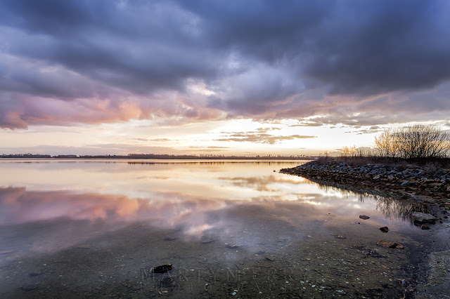 View from the shore at Grafham Water as the sunset colours fade from the stormy sky
