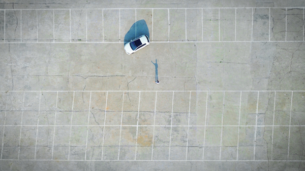 image of a parking lot from above; the parking lot is empty except for one white car, and a figure standing near the car, whose shadow reveals that the person is waving