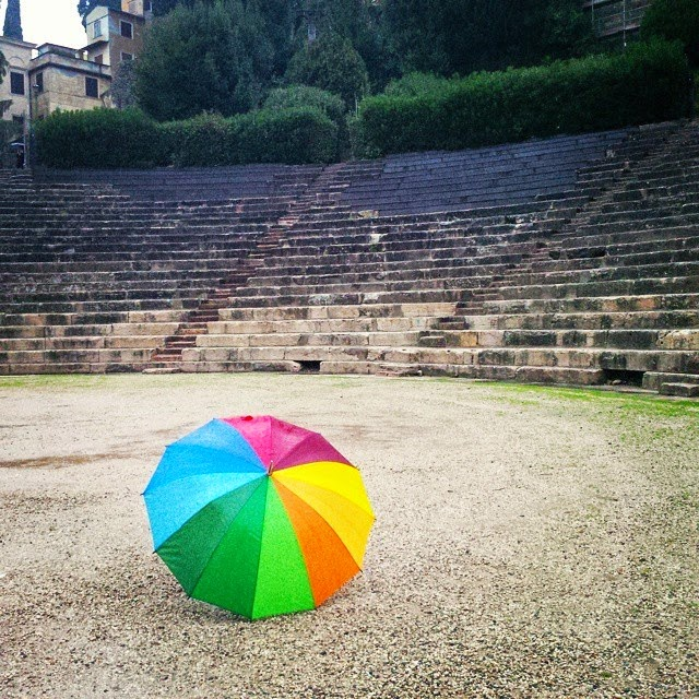 My rainbow umbrella is a pop of colour under the rain battering the Roman amphitheatre in Verona