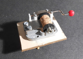 A small object topped with what appears to be the mechanical element of a music box.