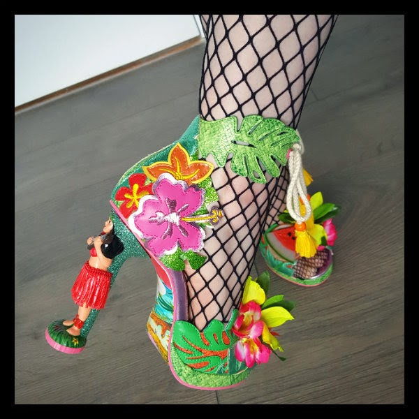 detailed view of hula girl heeled shoes on foot with fishnet tights