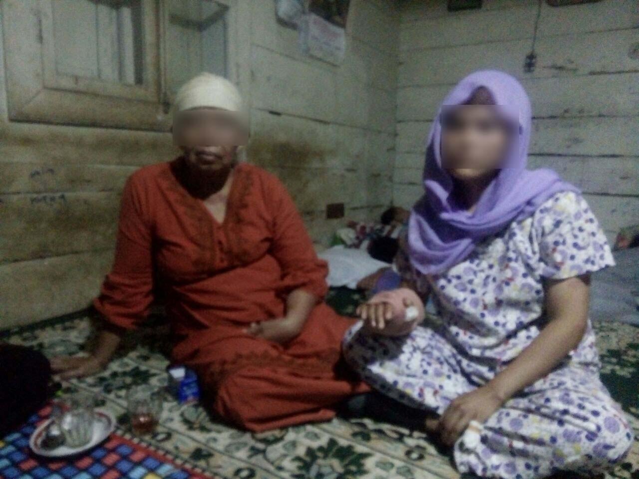 Istri almarhum korban pembantaian didampingi keluarga memberikan keterangan.
