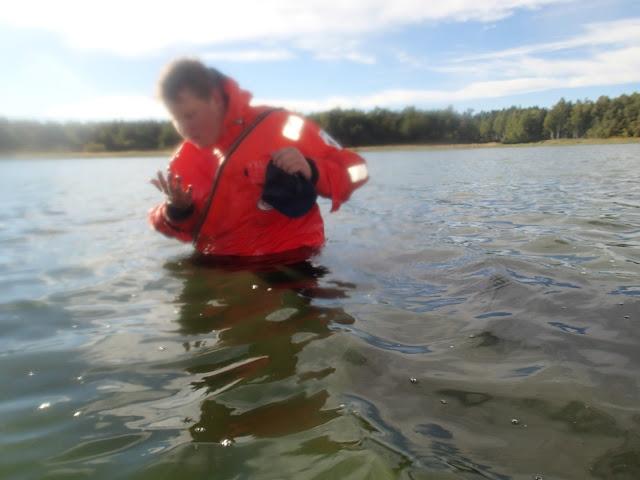 Pelastautumispukuinen henkilö seisoo vyötäröä myöten vedessä ja ihmettelee jotain kädessään