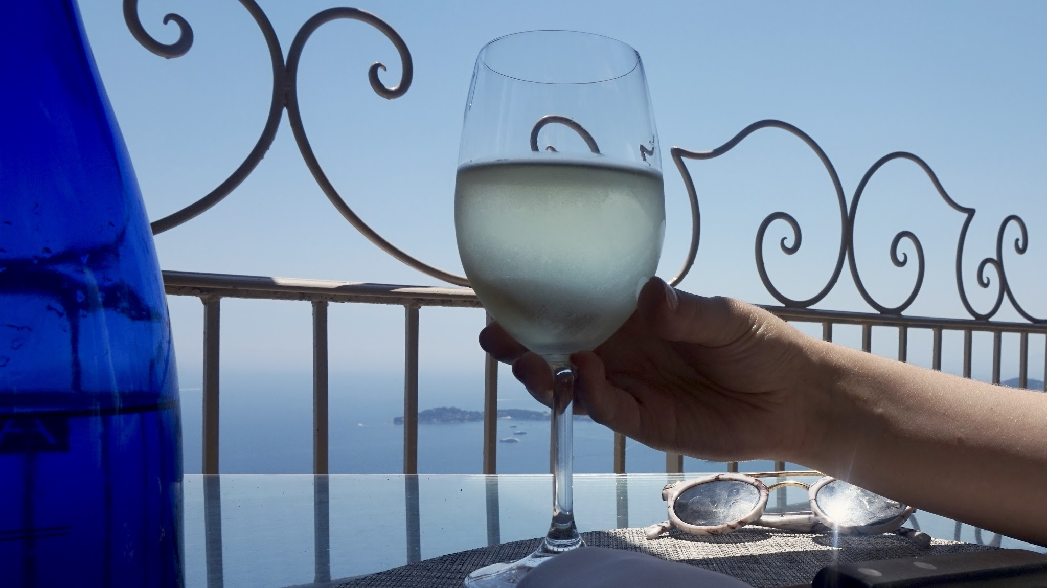 woman holds a glass of white wine in front of some railings overlooking the sea
