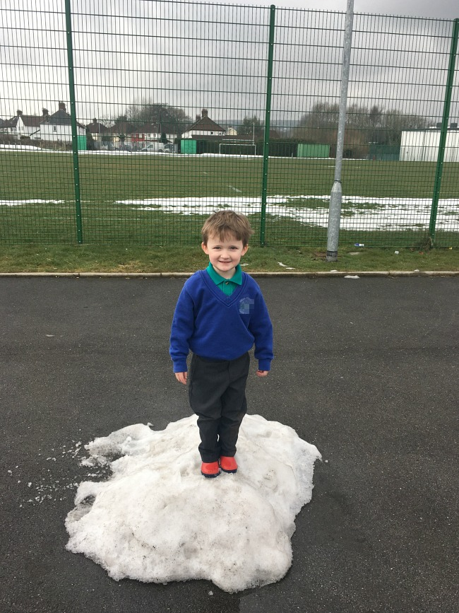 boy-standing-on-pile-of-snow