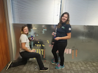 Two WCC AmeriCorps members in front of a bulletin board, one woman kneeling on the left, one woman standing.