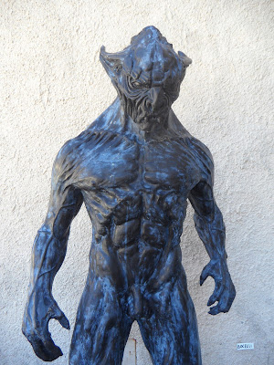 A humanoid monster stands in a menacing pose.