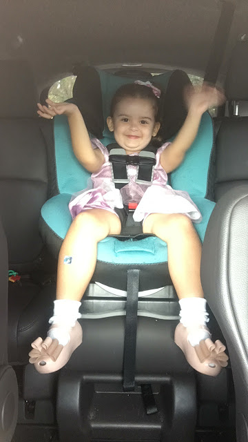Toddler sits happily in her carseat waving with both hands