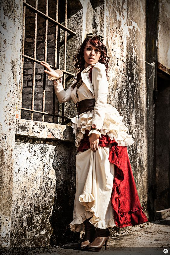 Woman wearing Steampunk clothing consisting of a dress with cream white and red ruffles, boots, a harness and goggles.