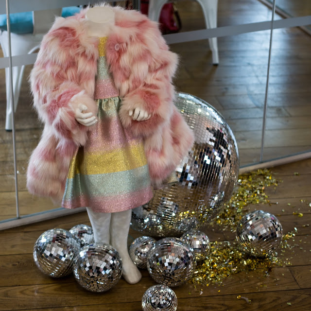 A pink and white faux fur child's coat over a sparkly striped children's dress