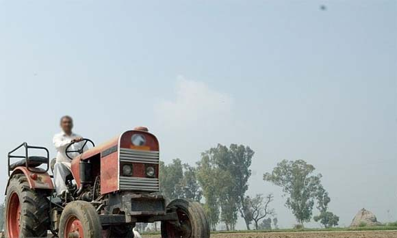 farmer working in the field with tractor in india