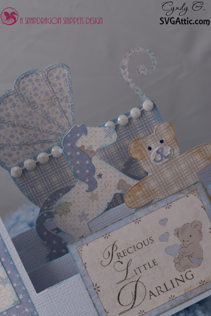 close up of card showing baby carriage, teddy bear and rocking horse