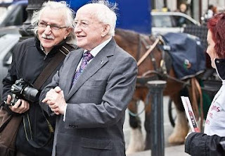 Michael D Higgins and?  standing in front of a horse