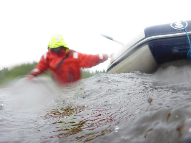 Pelastautumispukuinen henkilö kahlaa aallokossa ja pitelee kiinni kumiveneestä