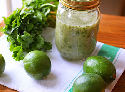 Cilantro Lime Vinaigrette in a jar with limes and cilantro next to it