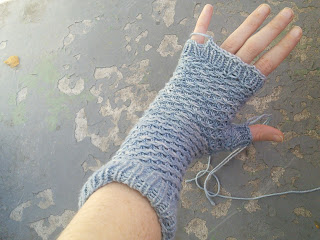 A blue-white fingerless mitten knit in fingering-weight yarn. It has a ribbed top and bottom cuff and is made in a spiraling stitch pattern. The ends of the yarn at the thumb and at the palm are not woven in.