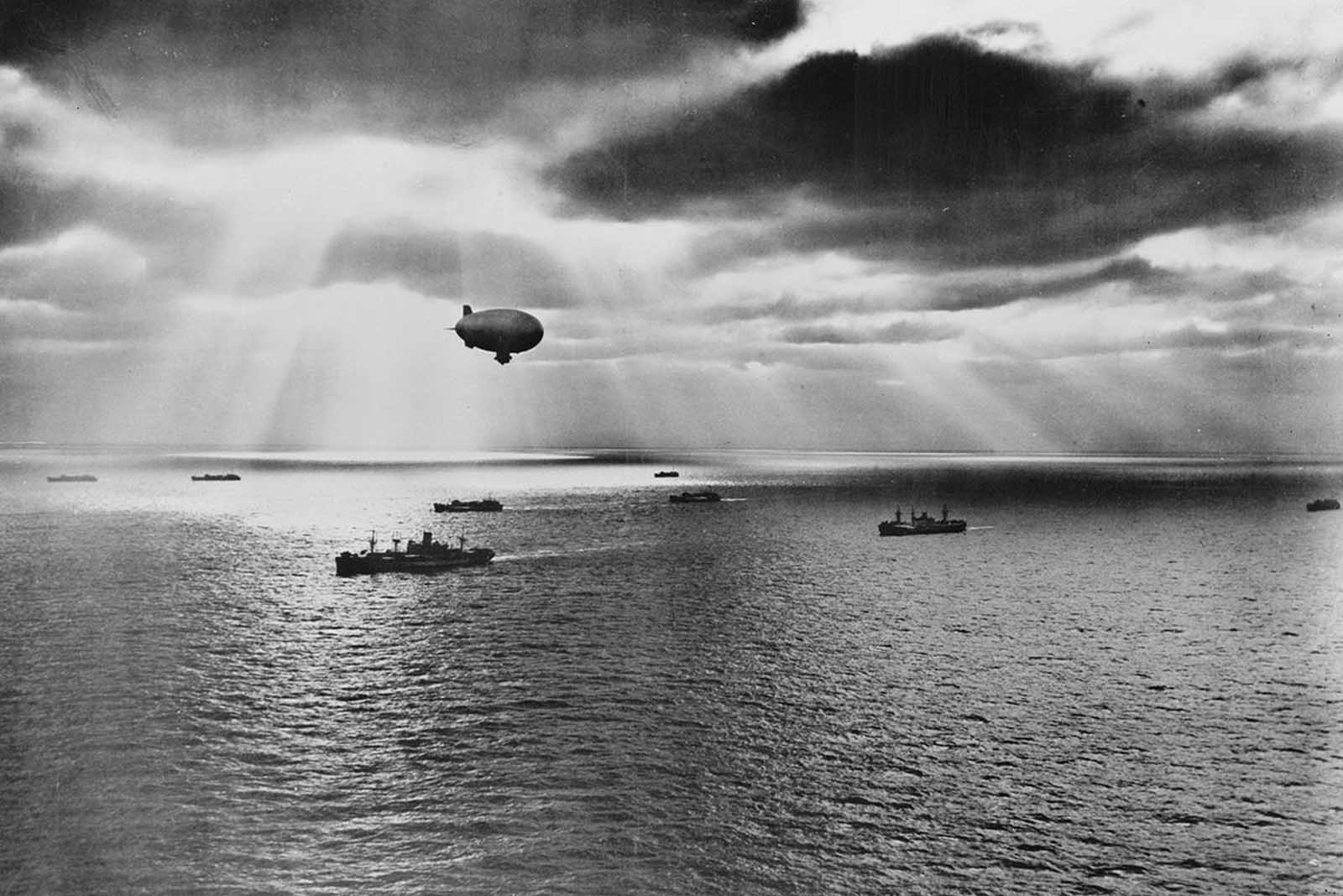 Sunset over the Atlantic finds a United Nations convoy moving peacefully towards it destination during World War II. A U.S. Navy blimp, hovering overhead, is on the lookout for any sign of enemy submarines, in June of 1943.