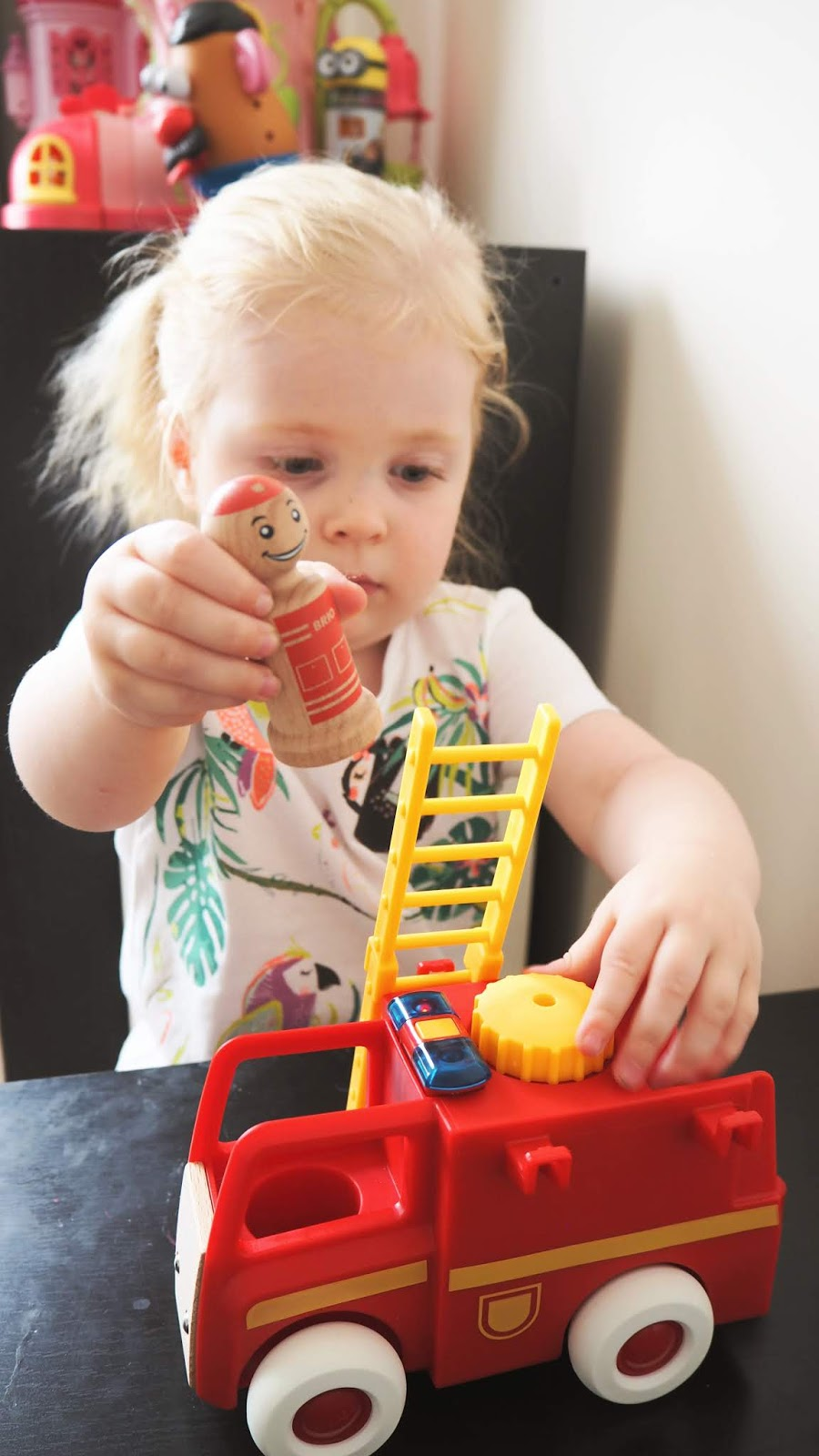 Elise is getting one of the little wooden peg people to climb up a ladder which she has rested against the fire truck